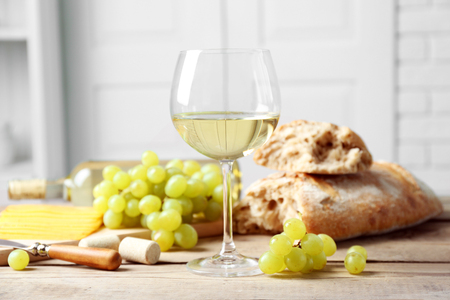 Still life of wine, grape, cheese and bread on light background Stock Photo