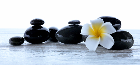 Wet spa stones with flower isolated on white