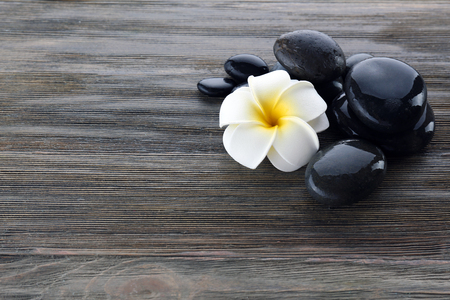 Wet spa stones with flower on wooden background