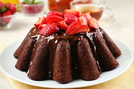 Tasty chocolate muffin with glaze and berries on table close up