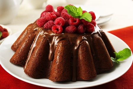 Tasty chocolate muffin with glaze and raspberries on table close up Stock Photo