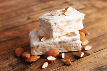 Sweet nougat with almonds on wooden background 免版税图像