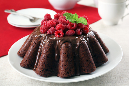 Tasty chocolate muffin with glaze and raspberries on table close up Banque d'images