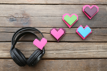 Black headphones with hearts on wooden background Banque d'images