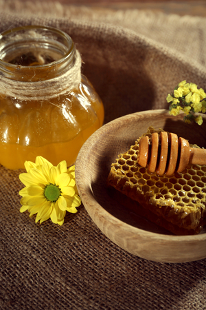 Pot of honey, honeycomb and dipper in bowl on sackcloth Banque d'images