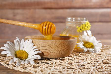 Honey and flowers on wicker mat