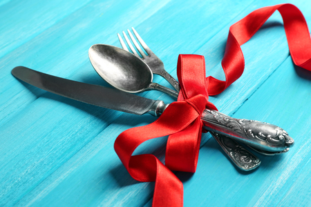 Cutlery tied with ribbon on wooden background
