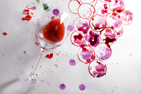 Wineglass of spilled wine with watercolors stains on paper background Stock Photo