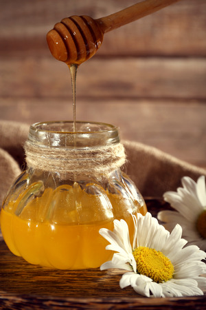 Honey pouring from wooden dipper in pot on tray with chamomile on sacking on wooden background