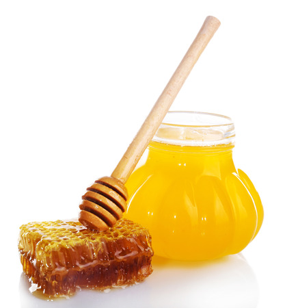 Pot of honey, wooden dipper and honeycomb isolated on white Banque d'images