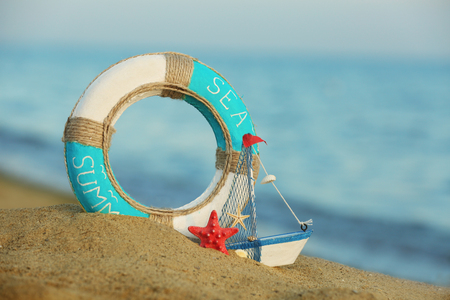 Beautiful life buoy in the sand with boat toy on unfocused sea background Imagens