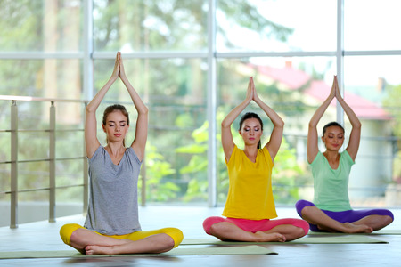 Young women meditating in yoga pose Stock Photo
