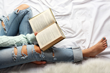 Woman in blue jeans reading book on bed top view point Stock Photo