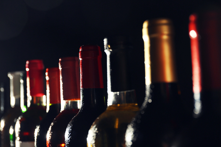 chilled wine bottles in a row on black background
