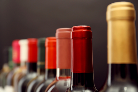 wine bottles in a row on dark grey background 版權商用圖片