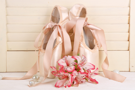 Decorated with flowers ballet shoes on wooden background