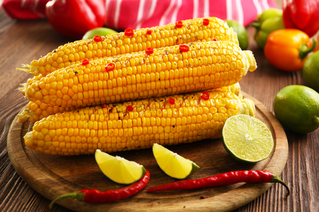 Grilled corn served with vegetables on rustic round plate Stock Photo