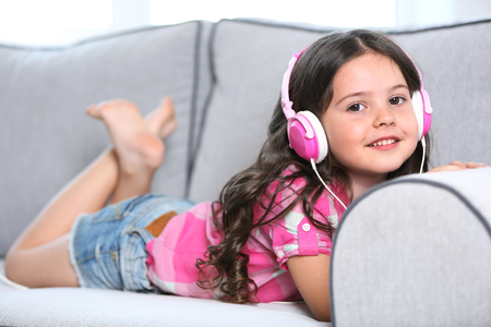 Smiling little girl listening music with pink headphones on sofa in light room