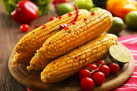Grilled corn served with vegetables on rustic round plate Stock fotó