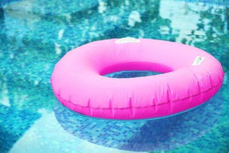 Pink pool float, pool ring in cool blue refreshing blue pool