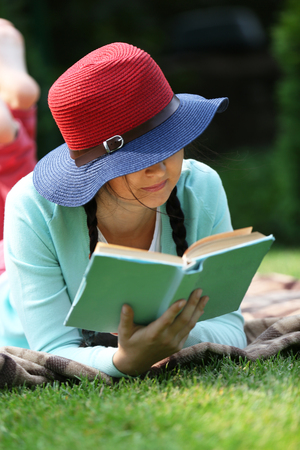 Young woman with book lying on green grass outdoors Фото со стока