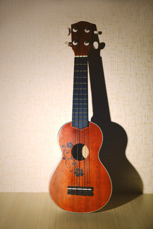 Beautiful Hawaiian acoustic guitar on light wallpaper background
