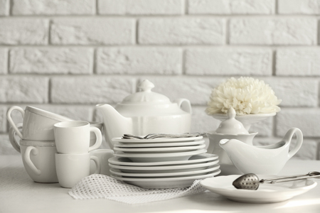 Clean dishes on table on brick wall background