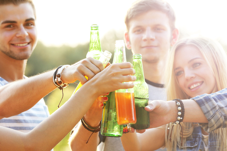 View on smiling friends clinking bottles in the forest, close-up Stock Photo