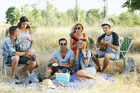 Young hippie people relaxing in the forest outdoors Banco de Imagens