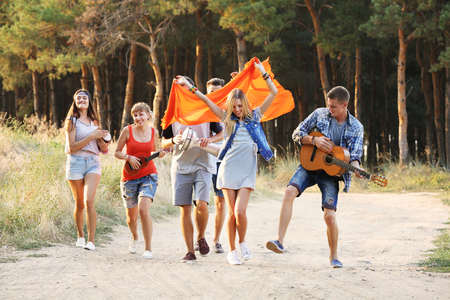 Happy smiling friends playing musical instruments in the forest outdoors Imagens