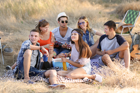 Happy friends have fun on picnic, outdoors