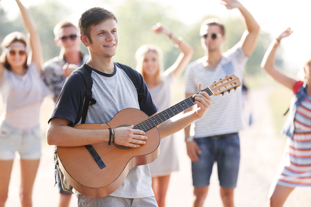 Attractive young man plays guitar against dancing friends, outdoors