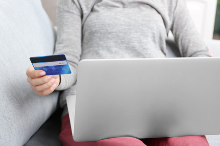 Concept for Internet shopping: woman with digital tablet and credit card sitting on sofa, at home Stock Photo