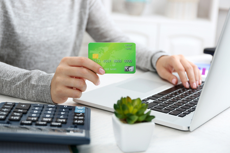 Concept for Internet shopping: hands with laptop and credit card