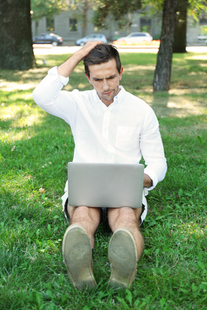 Man with laptop sitting on green grass in the park