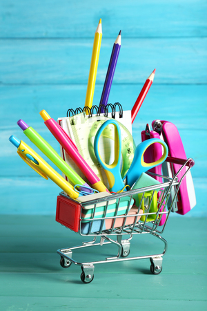 Bright stationery objects in mini supermarket cart on blue wooden background 스톡 콘텐츠
