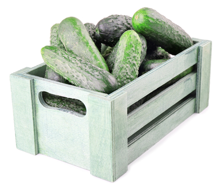 Ripe cucumbers in wooden box isolated on white Banque d'images