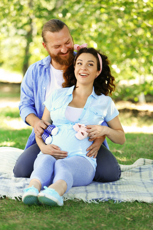 Beautiful pregnant woman with her beloved husband with baby booties in the park Reklamní fotografie