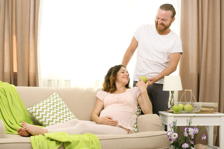 Handsome man and his lovely pregnant woman in the room Reklamní fotografie