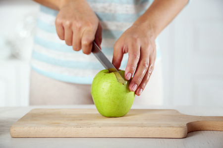 Female hands slicing apple for pie, close-up, on light background