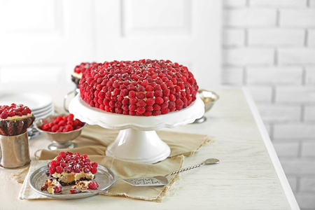 Sweet cake with raspberries on light background