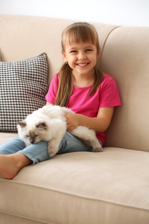 Little cute girl with kitten on sofa at home