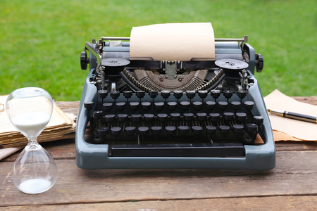 Vintage black typewriter with papers and pen on wooden table, outdoors