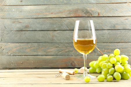 A glass of white wine and green grapes on wooden background 写真素材