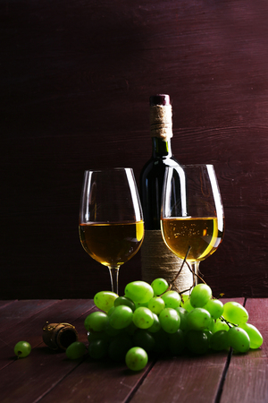 Bottle and glasses of wine with grape on wooden background Stock Photo