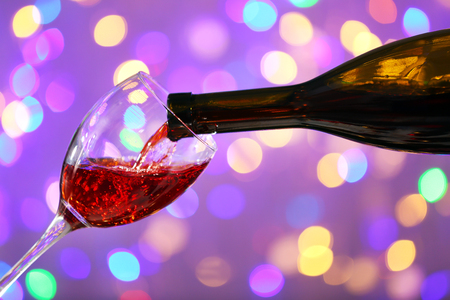 Wine pouring in glass on bright background Stock Photo