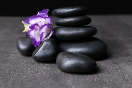 Balanced pebbles with beautiful flower on dark grey table
