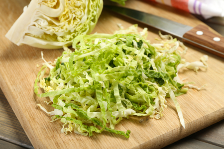 Cut savoy cabbage on wooden cutting board Stock Photo