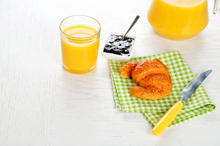 Tasty croissant and orange juice on green checkered napkin Stock Photo