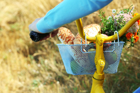 Young woman driving bike with basket of fresh foodstuffs, close-up